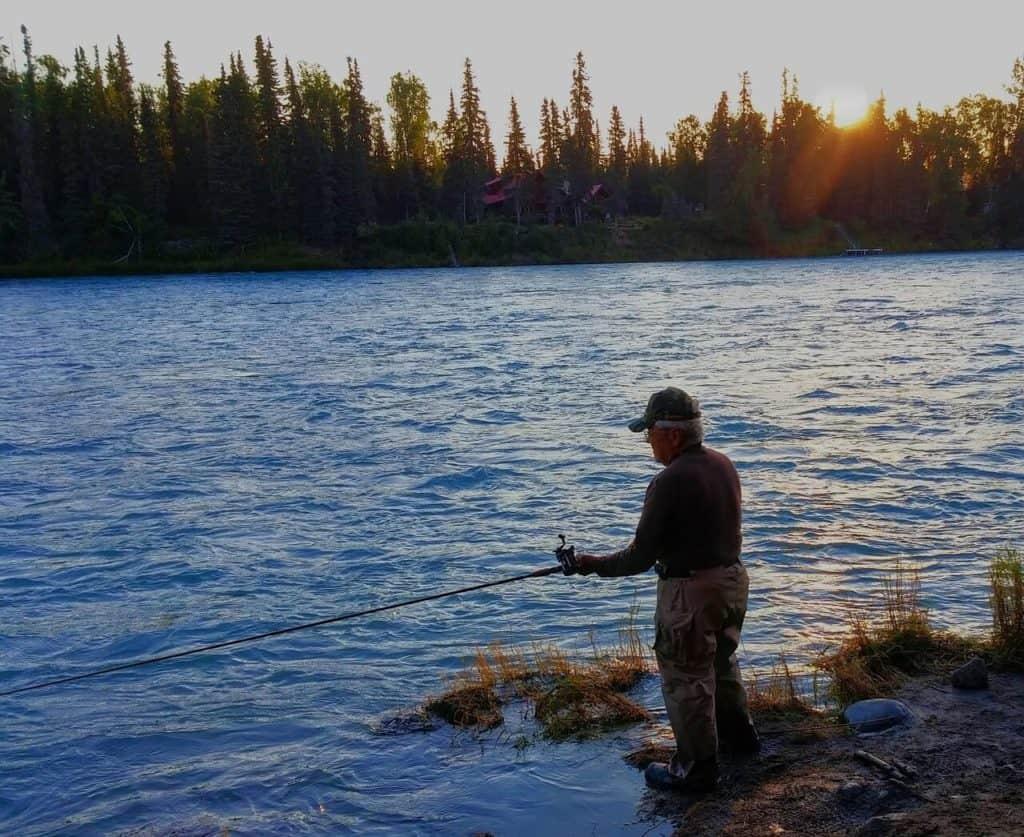 Рыбак на реке со спиннингом